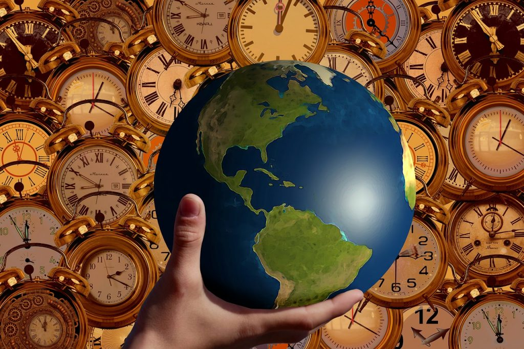 Hand holding a globe with clocks around the world